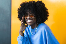 Stylish Young African American Female With Curly Hair In Trendy Sunglasses Looking Away While Standing Against Yellow Wall