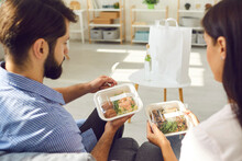 View Over The Shoulder Man And Woman Holding Containers Of Healthy Takeaway Food Delivered By Delivery Service. Couple Sitting On Sofa In Living Room And Enjoying Modern Service. Food Delivery Concept