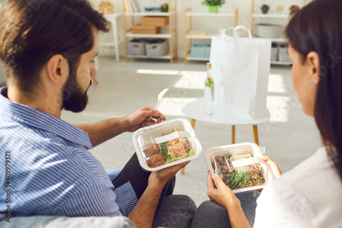 Obraz View over the shoulder man and woman holding containers of healthy takeaway food delivered by delivery service. Couple sitting on sofa in living room and enjoying modern service. Food delivery concept - fototapety do salonu