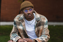 Young Black Guy In Trendy Checkered Shirt Frowning And Looking Away While Chilling On Street Of Modern City