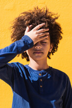 Disappointed Curly Haired African American Teen Boy With Eyes Closed Slapping Forehead While Standing Against Bright Yellow Wall