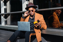 Serious African American Male Wearing Trendy Outfit And Accessories Sitting In Street With Laptop And Plastic Card And Making Purchase Online