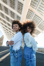 Low Angle Side View Of Smiling Teen Black Sister And Brother With Afro Hair Wearing Denim Overalls Standing Back To Back On Urban Street