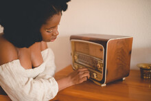 Side View Of Young African American Female Sitting At Table And Tuning Old Fashioned Radio Receiver While Resting At Home