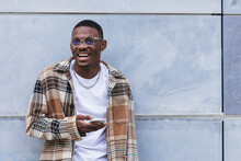 Happy African American Man In Trendy Checkered Shirt And Glasses Laughing And Browsing Smartphone While Leaning On Wall Of Modern Building On City Street