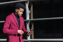 Young Black Guy In Trendy Suit Smiling And Touching Forehead While Reading Good News On Smartphone Standing On Street Near Contemporary Building
