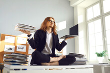 Calm Barefoot Busy Office Worker In Suit Sitting In Lotus Yoga Pose On Desk With Papers, Holding Paperwork Pile And Laptop, Breathing Deeply, Meditating And Relaxing. Balance And Stress Relief At Work
