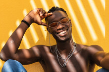 Positive Young Shirtless African American Male In Stylish Sunglasses And With Metal Necklaces Sitting Against Yellow Wall With Striped Shadow