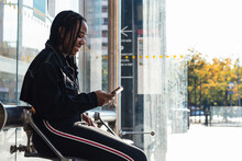 Side View Of Cheerful Black Woman In Casual Clothes Smiling And Looking Away While Sitting On Bench On Modern Bus Stop In City