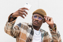 Trendy African American Male In Casual Clothes And Glasses Frowning And Taking Selfie Against Gray Wall On City Street