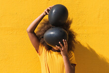 Unrecognizable Curly Haired Teen African American Girl In Yellow Shirt Covering Face With Black Balloons While Standing Against Bright Yellow Wall