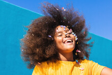 Low Angle Of Happy Carefree Teen African American Girl With Long Curly Hair And Colorful Confetti On Face Having Fun Against Blue Wall In Sunny Summer Day