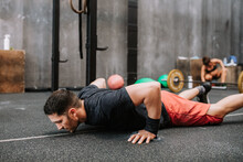 Concentrated Male Athlete In Sportswear Doing Push Ups While Exercising In Gym During Functional Workout