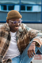 Young Black Guy In Trendy Checkered Shirt Frowning And Looking Down While Chilling On Street Of Modern City