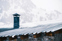 Chimney On Roof Of Small Residential House Located In Mountainous Countryside Covered With Snow On Cloudy Winter Day