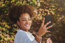 Attractive African American Female With Curly Hair And In Casual Clothes Taking Selfie On Smartphone During Stroll In Tropical City