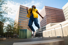 Happy Black Woman In Trendy Clothes Laughing And Leaping Up On Street Of Modern City Looking At Camera