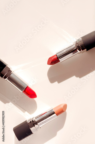 Fashion colorful lipsticks on beige background flat lay top view copy space. Beauty and cosmetics background. Decorative cosmetics, makeup, women's lipstick, beauty brand, product design © olgaarkhipenko