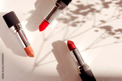 Fashion colorful lipsticks sun shadows from flowers on beige background flat lay top view. Beauty and cosmetics background. Decorative cosmetics makeup women's lipstick beauty brand product design © olgaarkhipenko