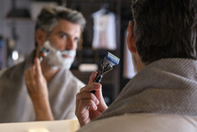 Stock Photo Of Middle Aged Man With Grey Hair Using Shaving Cream To Shave His Beard.