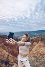 Cheerful Young Female Tourist Taking Selfie On Smartphone While Standing Among Rocky Sandstone Formations In Highlands