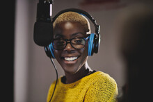 Cheerful Black Woman In Headphones Working In Broadcast Station And Speaking In Modem Microphone