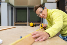 Low Angle Of Concentrated Middle Aged Female Carpenter In Uniform And Protective Goggles Measuring Wooden Plank With Roulette During Work At Table