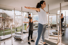 Group Of People In Activewear Standing On Pilates Reformers In Five Pointed Star Pose And Practicing Yoga Under Supervision Of Trainer In Modern Gym