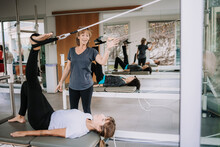 Female In Sportswear Lying On Pilates Cadillac And Stretching Legs With Straps Under Control Of Professional Trainer In Modern Gym