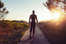 Back View Of Fit Professional Swimmer Walking Along Wooden Pathway Towards Sea For Training At Sunset