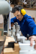 Side View Of Concentrated Middle Aged Male Carpenter In Headphones Working On Bench Saw Machine In Joinery
