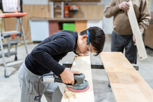 Side View Of Concentrated Boy In Casual Clothes And Goggles Smoothing Wooden Panel With Random Orbital Sander While Helping Crop Anonymous Craftsman At Workshop