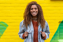 Optimistic Young Black Female Millennial With Curly Hair In Stylish Clothes Smiling While Looking At Camera Against Yellow Wall