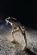 Full Body Of Young Female In Activewear Standing In Half Squat Pose On Sandy Dusty Way At Night Time