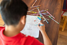 From Above Of Crop Anonymous Boy In Red Polo Shirt Doing Homework Assignment With Colorful Pens And Markers While Sitting At Wooden Table