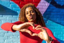 Confident Young Ethnic Lady With Afro Hair In Casual Wear Pouting Lips And Showing Heart Sign With Hands While Standing On Street Near Brick Wall With Colorful Graffiti
