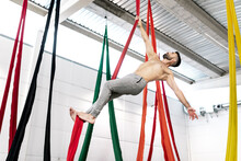 Full Body Strong Barefoot Male Gymnast Hanging On Aerial Silk Under Ceiling While Practicing Aerial Dance In Modern Studio