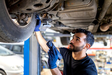 Serious Male Mechanic With Flashlight Examining Lifted Car While Working In Automobile Service