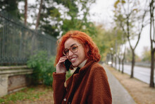 Delighted Female With Red Hair And In Autumn Coat Standing At The Park And Speaking On Mobile Phone While Enjoying Conversation