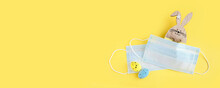 Medical Protective Face Mask, Wooden Bunny And Colorful Easter Eggs Isolated On Yellow Background. Concept Of Easter Holiday During Pandemic Coronavirus. Flat Lay, Top View, Copy Space. Banner.