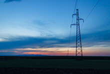 Beautiful Twilight View Behind Transmission Towers In A Field