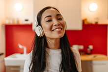Nice Girl In Massive Headphones Poses In Kitchen And Enjoys Music