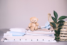 Pile Of Clean Baby Clothes, Skin Care Cosmetic, Teddy Bear Toy And Laundry Basket For Newborn. Waiting And Preparing For Child Birth Or Travel With Baby.