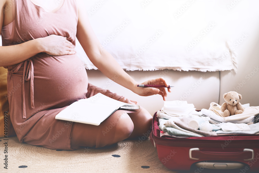 Fototapeta Pregnant woman packing bag for maternity hospital, making notes, checking list in diary. Expectant mother with suitcase of baby clothes and necessities preparing for newborn birth during pregnancy.