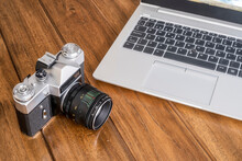 An Old 35 Mm Reflex Camera On A Wooden Table Next To A Modern Laptop, A Contrast Between Modern And Old, Horinzontal