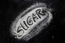 Word Sugar Written On Sugar Powder On Dark Table