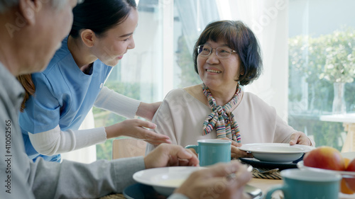 Fotografie, Obraz Attractive young senior asian citizen couple happy sit, talk, eat soup for healthy nutrition breakfast meal on dining table at home in morning in routine lifestyle in old asia nursing in-home care