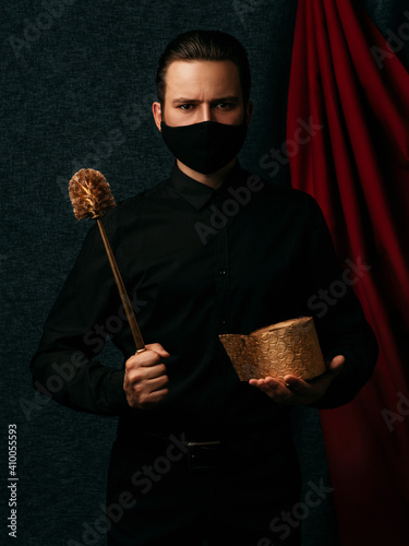 Photo protesting Russian man with a gold toilet brush in his hand wearing a medical ma