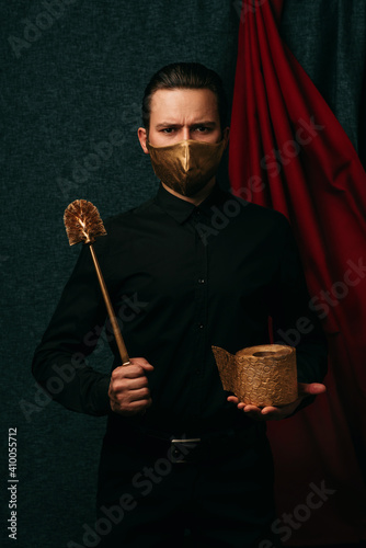 Photo protesting man with a gold toilet brush and a roll of toilet paper wearing a med