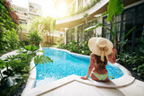 Beautiful woman in big straw hat sitting on edge of swimming pool and looking at beautiful water and lush plants around, view from the back